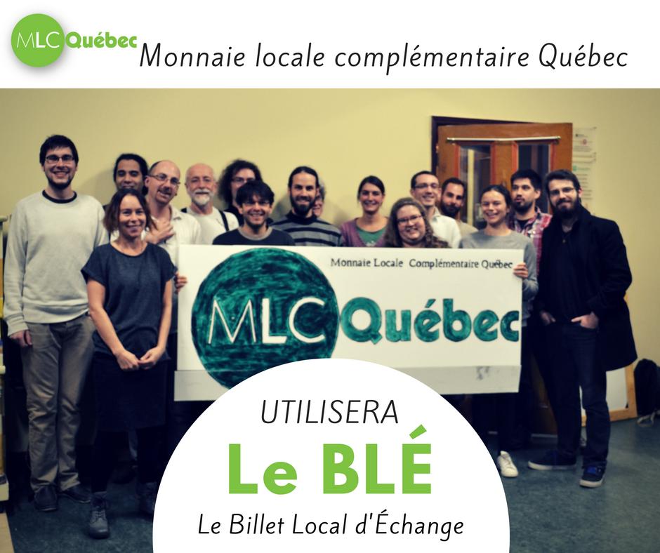 Photo avec l'ajout des mots Le BLÉ : Billet Local d'Échange. Une vingtaine de personnes posent en groupe lors de l'assemblée constituante, tentant une bannière MLC Québec.
